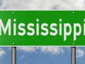 Green highway sign with clouds in the background showing the state Mississippi